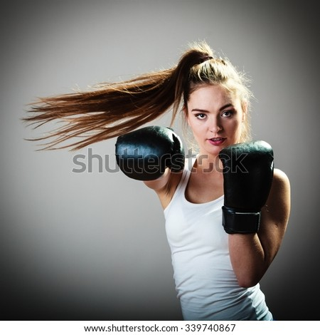 Martial arts or self defence concept. Sport boxer woman in black gloves. Fitness girl training kick boxing. - stock photo