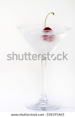 martini cocktail with a single cherry in martini glass on white background. - stock photo