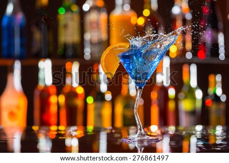 Martini drink served on bar counter with blur bottles on background - stock photo