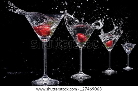 Martini drinks with splashes, isolated on black background - stock photo