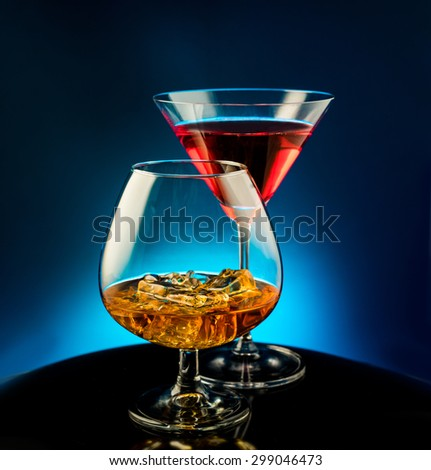 Martini glass and cognac on a blue background - stock photo