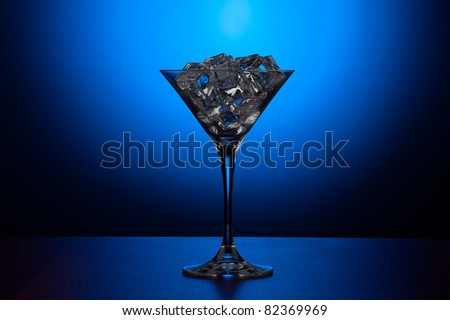 Martini glass with ice on gradient blue background - stock photo
