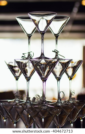 martini glasses in the form of a cascade or pyramid lit light at the wedding party - stock photo