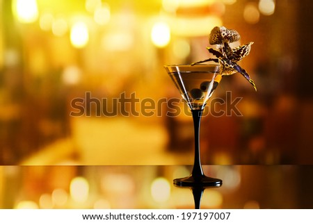 martini , green olives and orchid flower on mirror table in bar - stock photo