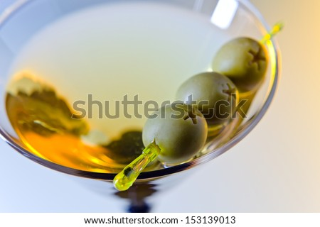 martini with green olives , focus on oliwes - stock photo