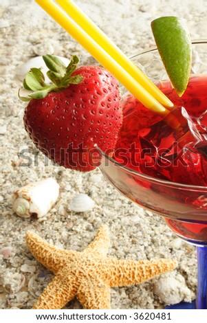 Martini with slice of lemon on the sand - stock photo
