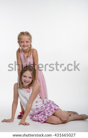 Marvelous children smile and look right in the camera with their big blue eyes. The elder sister sits on the ground, while the young one stands and puts her hands on shoulders of her sibling. - stock photo