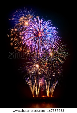 Marvelous multi-colored fireworks display on black background, reflected on water - stock photo