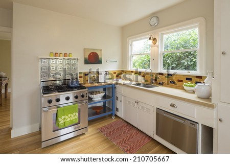 Marvelous sleek White Kitchen with yellow mosaic tiles and stainless steel oven - stock photo