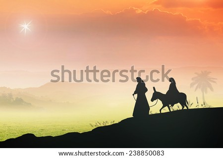 Mary and Joseph with a donkey on Christmas Eve. Bethlehem city in the background. Nativity scene story, Glory to God in the highest, and on earth peace among those with whom he is pleased concept. - stock photo