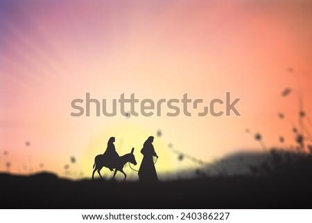 Mary and Joseph with a donkey on Christmas Eve. Bethlehem city in the background. Nativity scene story, Christmas background concept. - stock photo