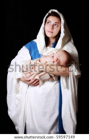 Mary looking to Heaven as she holds Jesus - stock photo