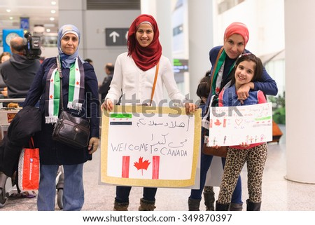 Maryam, 8, holds her handdrawn sign, alongside her family to welcome the first Syrian refugees at Toronto's Pearson International Airport on December 10, 2015. - stock photo