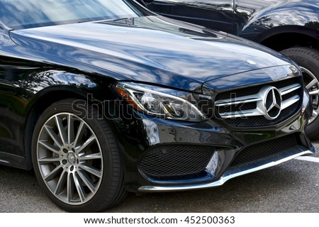 MARYLAND, USA - JULY 12, 2016: A black Mercedes-Benz C-400. Mercedes-Benz is a luxury car dealer and manufacturer. - stock photo