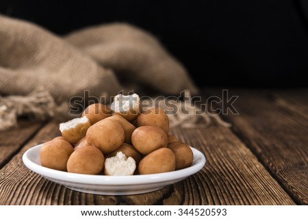 Marzipan Potatoes (German cuisine) on rustic wooden background - stock photo
