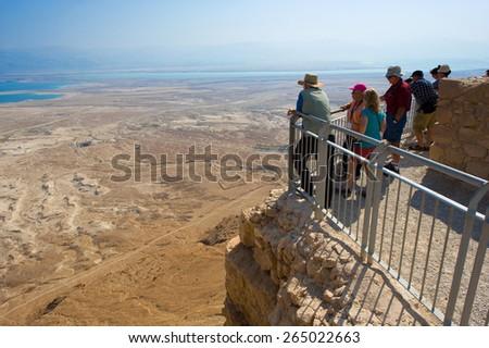 MASADA, ISRAEL - OCT 14, 2014: Tourists enjoying the view from Masada - stock photo