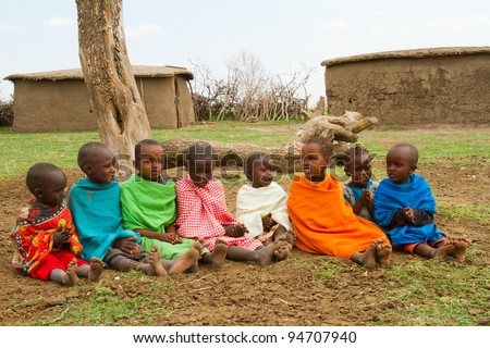 MASAI MARA, KENYA - AUG 24: Little unidentified Kenyan children from Masai tribe dressed with simple and dirty clothes on Aug 24, 2011 in Masai Mara, one of the famous national reserve parks in Kenya. - stock photo