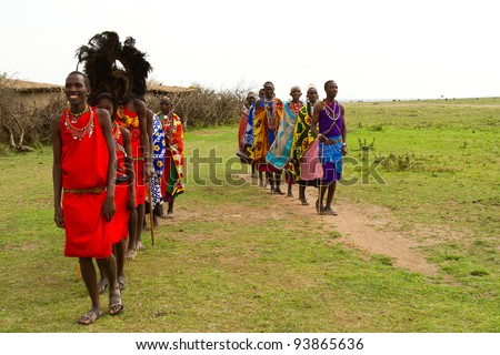 MASAI MARA, KENYA - AUGUST 24: A group of kenyan of Masai tribe performs a traditional dance to welcome their visitors on August 24, 2011 in a local village near Masai Mara National Park, Kenya. - stock photo