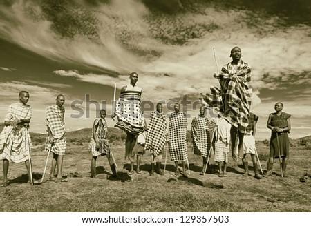MASAI MARA, KENYA - DECEMBER 2: Masai warriors dancing traditional jumps as cultural ceremony. As well as women sing and dance. Masai Mara National Park, December 2, 2011 in Kenya (stylized retro) - stock photo