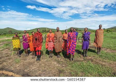 MASAI MARA, KENYA - DECEMBER 2: Masai warriors dancing traditional jumps as cultural ceremony. As well as their women sing and dance. Masai Mara National Park, December 2, 2011 in Kenya - stock photo