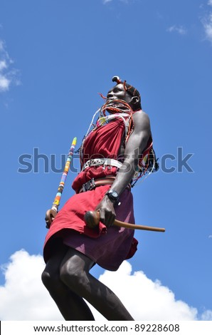 MASAI MARA, KENYA – OCTOBER 19, 2011: A young Masai welcomes tourists with the traditional jumping ceremony .  Masai Mara, October 19, 2011 Masai Mara - stock photo