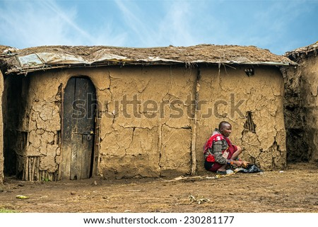 MASAI MARA, KENYA - OCTOBER 17, 2014: African woman from Masai tribe working in front of her village house. The Maasai are a Nilotic ethnic group living in southern Kenya and northern Tanzania - stock photo