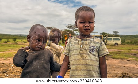 MASAI MARA, KENYA - OCTOBER 17, 2014: Two african boys from Masai tribe in their village. The Maasai are a Nilotic ethnic group living in southern Kenya and northern Tanzania - stock photo