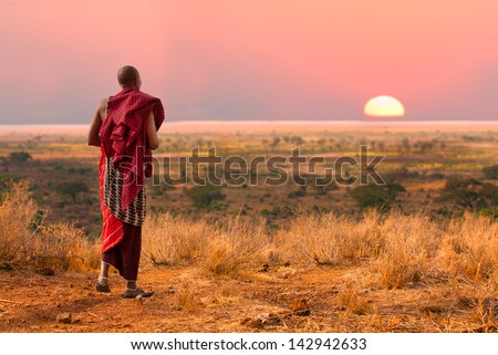 Masai warrior looks out over Serengeti at sunset - stock photo