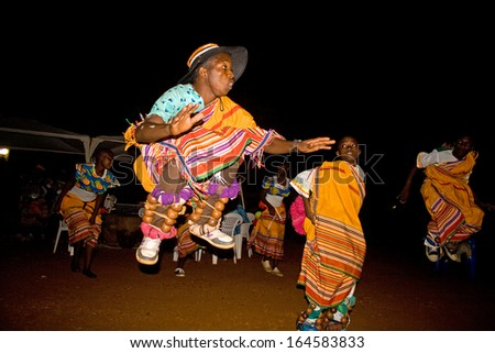 MASAKA, UGANDA - NOVEMBER 23: An unidentified dancing group performs a traditional dance during the night on November 23, 2013 in Masaka.  Dance tells the story of traditional life. - stock photo