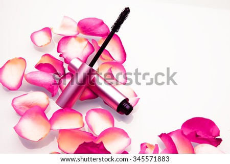 Mascara brush for long lashes with rose petals on white background. Cosmetics and beauty. Studio shot, Horizontal - stock photo