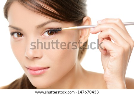 Mascara woman putting makeup on eyes. Asian female model face closeup with eye brush on eyelashes. - stock photo
