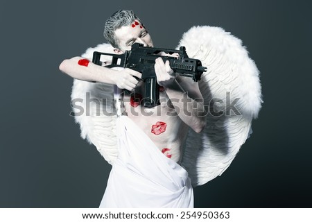 Masculine male angel Cupid with a gun instead of a bow and arrows of love. Valentine's day. Love concept. - stock photo