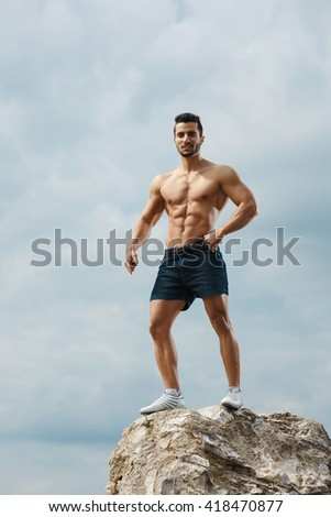 Masculinity in portrait. Shot of an attractive bearded strong man posing outdoors looking to the camera. - stock photo