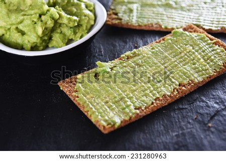 mashed avocado with crispbread and lemon - stock photo