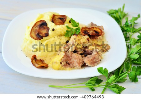 Mashed potatoes and julienne meat and mushrooms on a white plate on a wooden table - stock photo