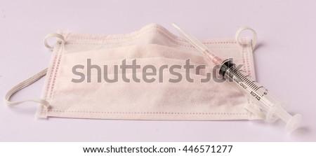 Mask and syringe isolated on white background - stock photo