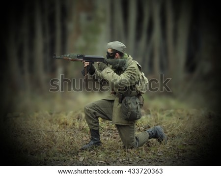 Masked airsoft player, who plays for Russian side of the army, old time scenery, blurred blackground, dark vigneting - stock photo