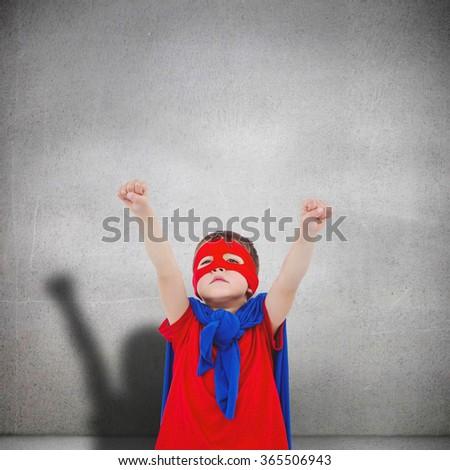 Masked boy pretending to be superhero against grey room - stock photo