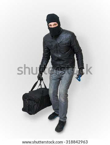 Masked burglar or thief with balaclava is sneaking with black bag. - stock photo