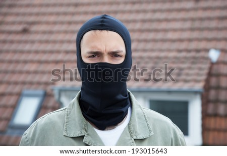 Masked burglar with roofs in the background - stock photo