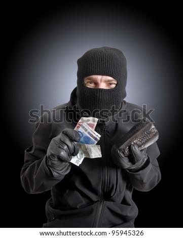 Masked criminal holding a stolen leather purse - stock photo