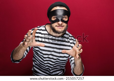 Masked criminal ready to fight. Portrait on red background  - stock photo