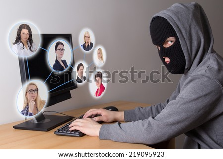 masked hacker stealing data from computers - stock photo