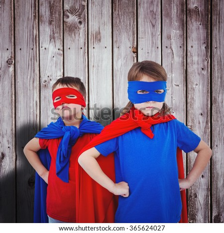 Masked kids pretending to be superheroes against digitally generated grey wooden planks - stock photo