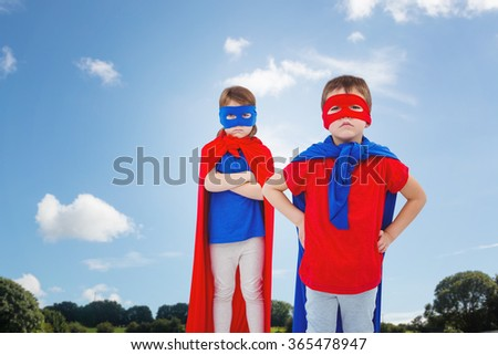 Masked kids pretending to be superheroes against green field - stock photo