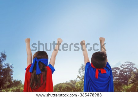 Masked kids pretending to be superheroes against park on sunny day - stock photo