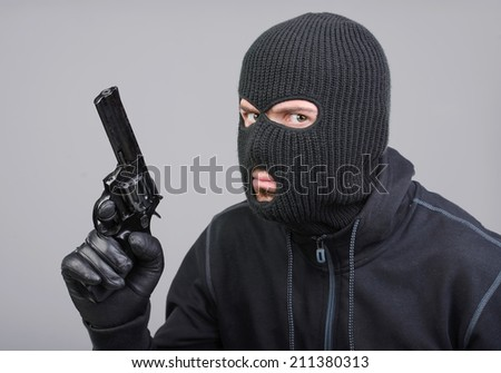 Masked robber with gun aiming into the camera - stock photo
