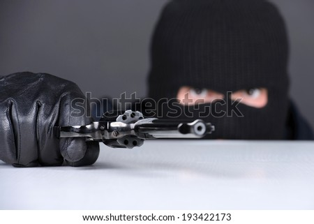 Masked robber with gun aiming into the camera against a black background - stock photo