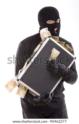 masked robbers with a suitcase full of money with an aggressive expression on his face - stock photo