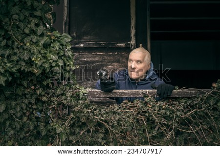 Masked senior escapee man aiming a gun, hiding on overgrown porch of old cabin. - stock photo